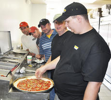 """<div class=""""source"""">Larry Rowell</div><div class=""""image-desc""""> Shaker's Pizza, owned by the J.R. Grant family, opened March 16 in Allen's Shell Mart on Wallace Wilkinson Boulevard. The business — take-out or city-wide delivery — offers a variety of pizzas in addition to wings, toasted subs, hamburgers, salads, and pasta dishes. At right, Les Couch, owner of the Mt. Vernon Shaker's Pizza, demonstrates pizza-making to J. R. Grant, Aerin Grant, Andy Grant, and employee Dwayne Rigdon.</div><div class=""""buy-pic""""></div>"""